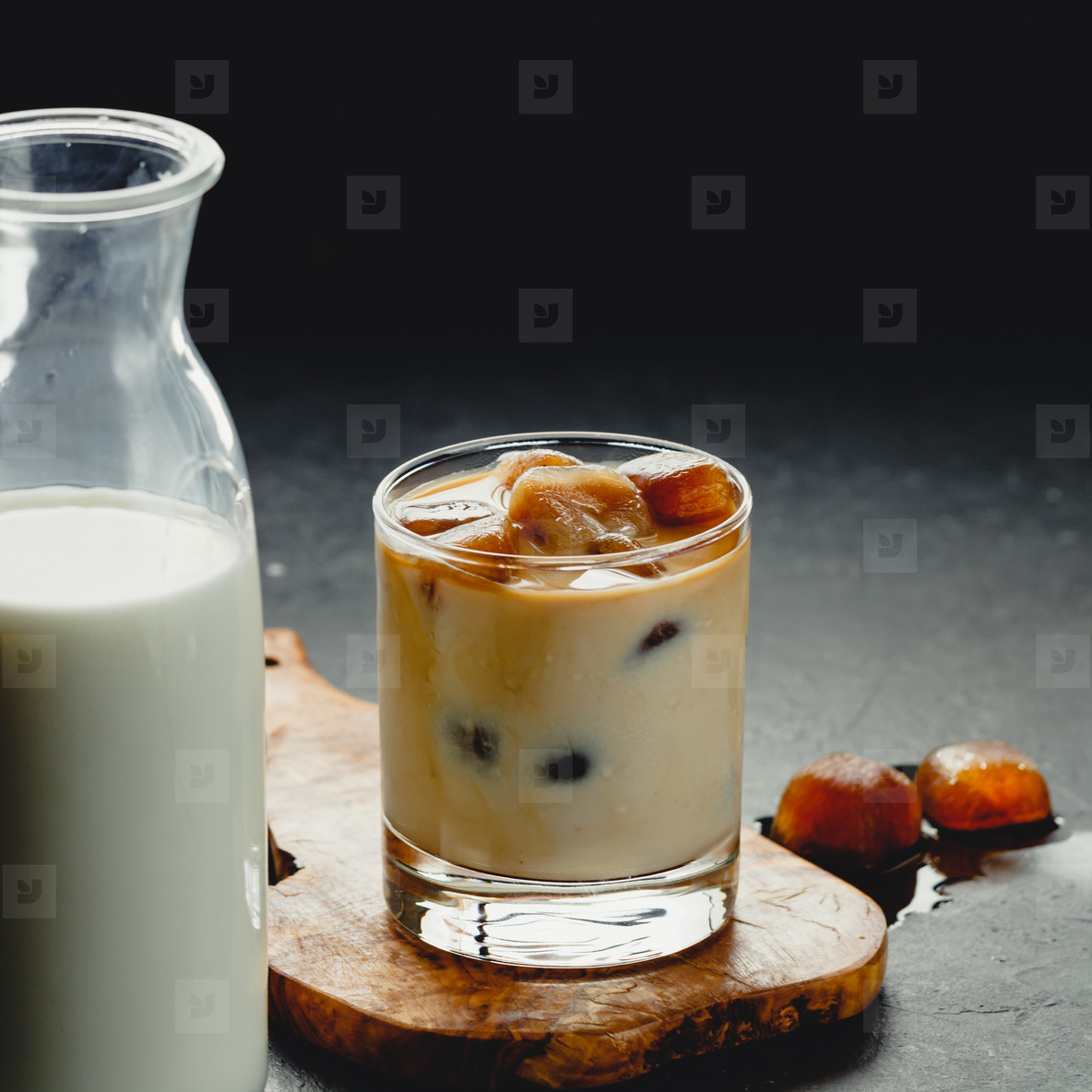 Coffee ice cubes with milk in a glass on a table  Refreshing cold drink