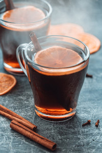 Christmas traditional hot beverage mulled wine with spices and orange slices in a glass cups on a table