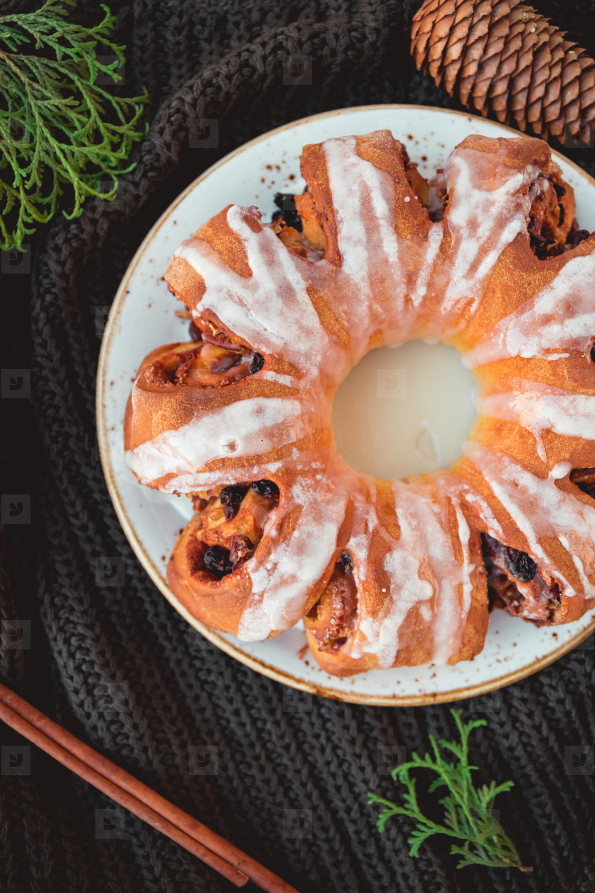 Creative flat lay  top view of Swedish tea ring Christmas cake with cinnamon  pecans and raisins on a warm knitted sweater  The concept of cozy winter Holidays and homemade bakery
