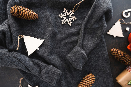 Top view of Christmas or winter time flat lay with grey warm woolen sweater fir cones and wooden toys