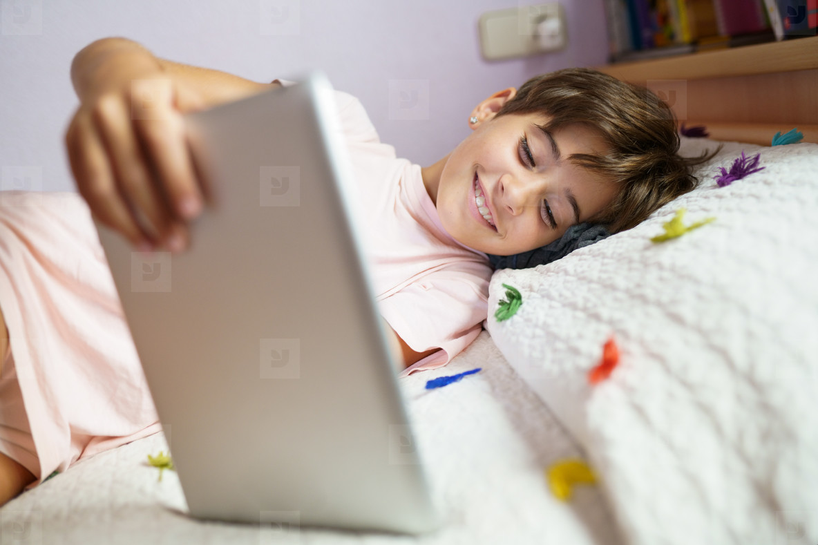 Cute girl using a tablet computer in her bedroom