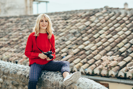 Young woman taking photographs with an old camera in a beautiful city