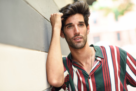 Attractive young man with dark hair and modern hairstyle wearing casual clothes outdoors