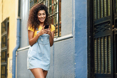 North African woman walking on the street looking at her smart phone