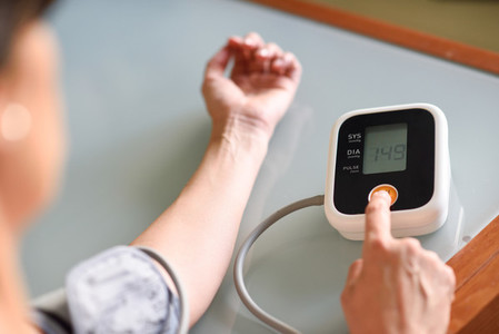 Woman measuring her own blood pressure at home