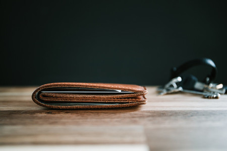 Brown leather wallet and keys on a wooden table with black background