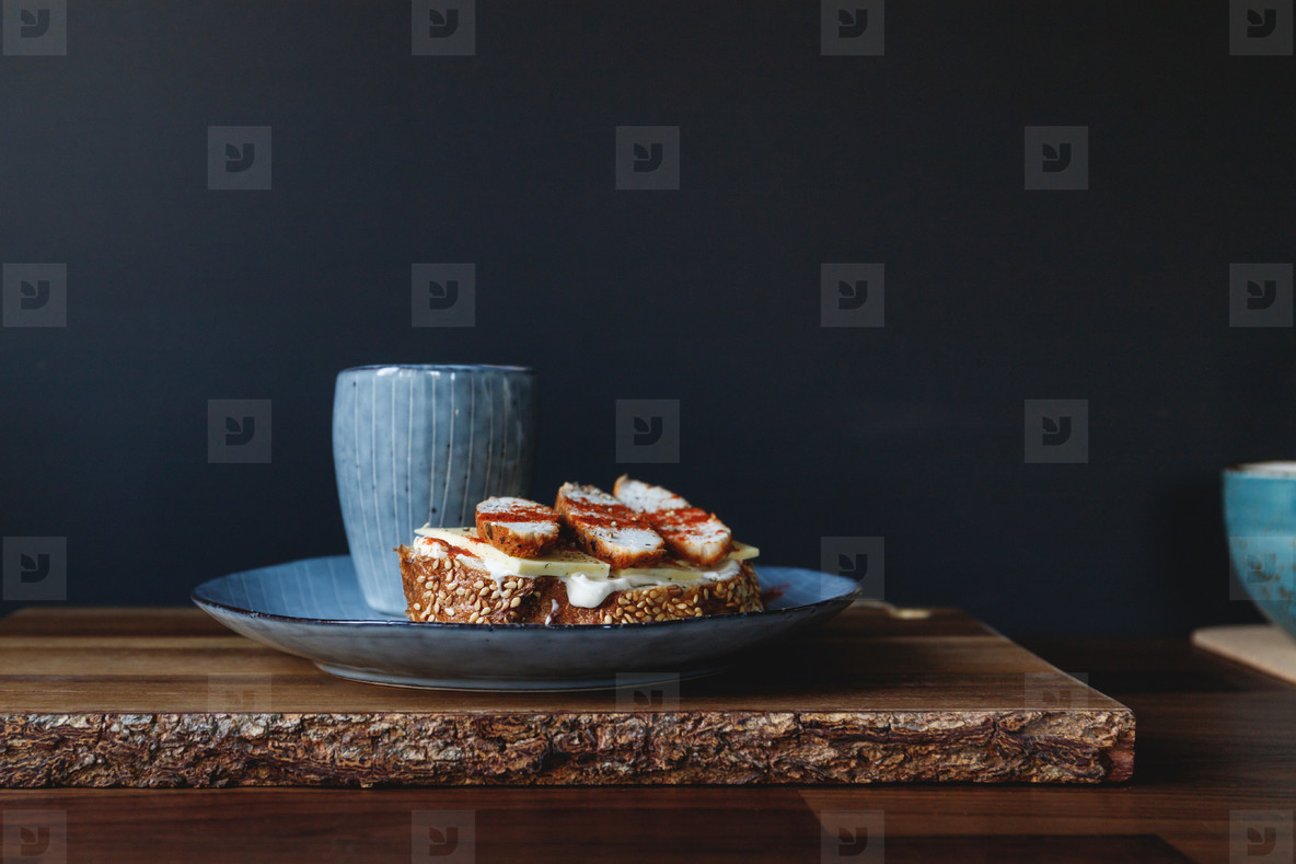 Healthy nutrition breakfast with espresso coffee and sandwich with cheese and turkey breast in a blue plate served on a rustic wooden tray
