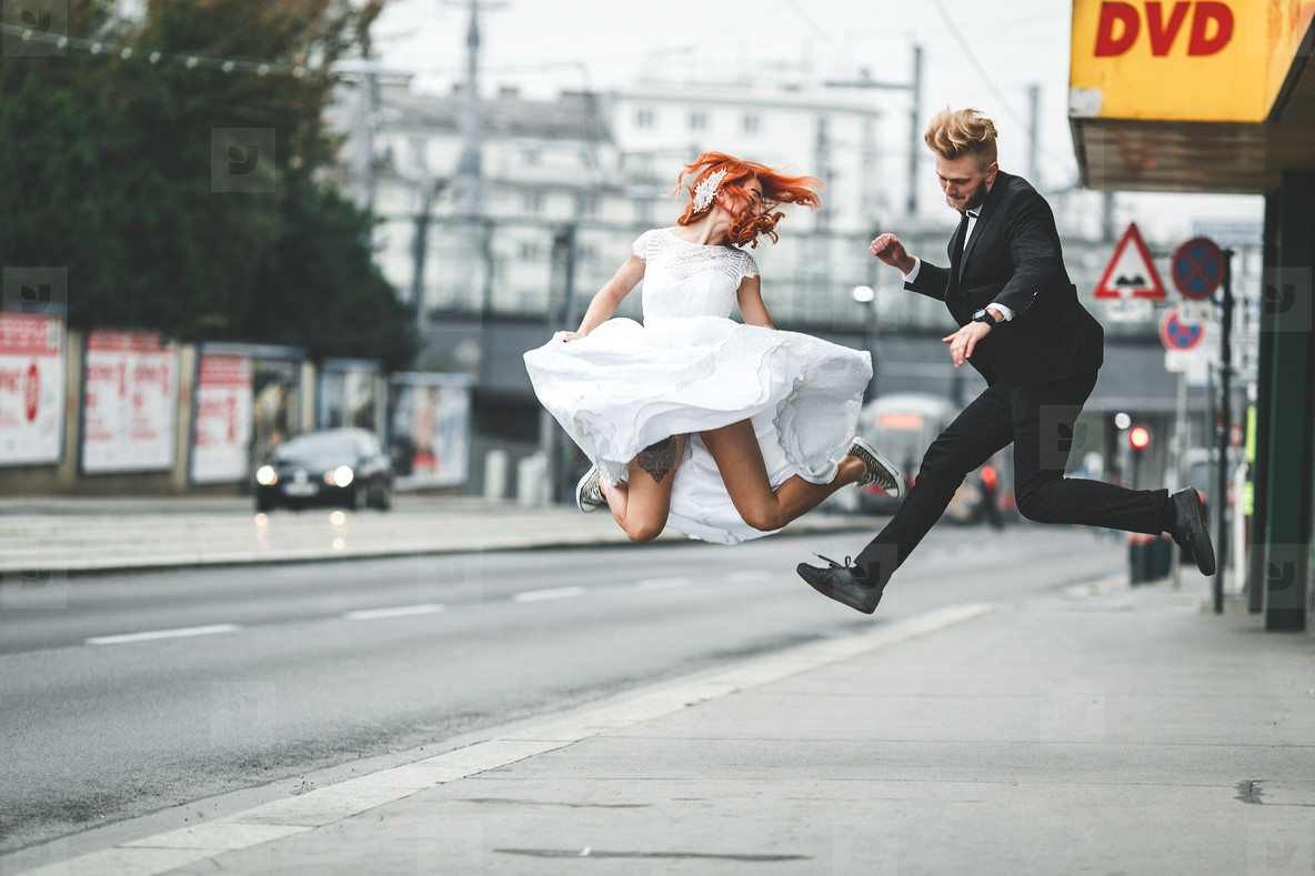 Wedding couple jumping in the city
