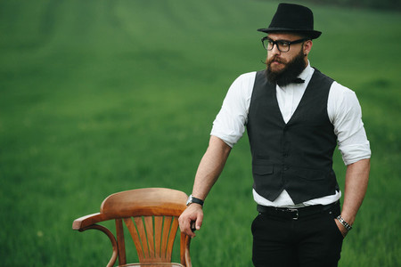 A man with a beard thinking in a field near chair