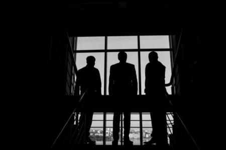 Three businessmen standing at the window with a city view