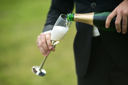 Groom pours a glass of champagne