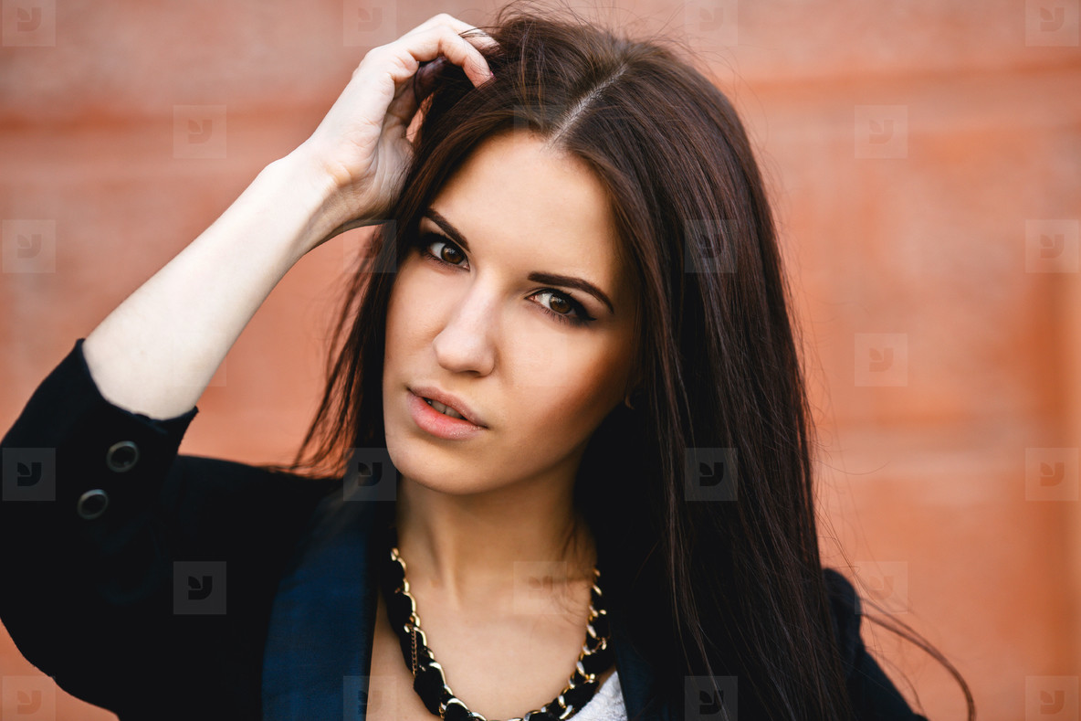 Beautiful female model posing against the wall