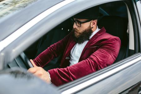 Man with a beard driving a car