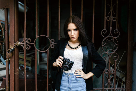 Beautiful girl standing against a wall with a camera