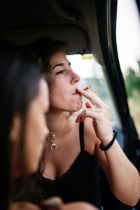 Two young lesbians smoking inside a car