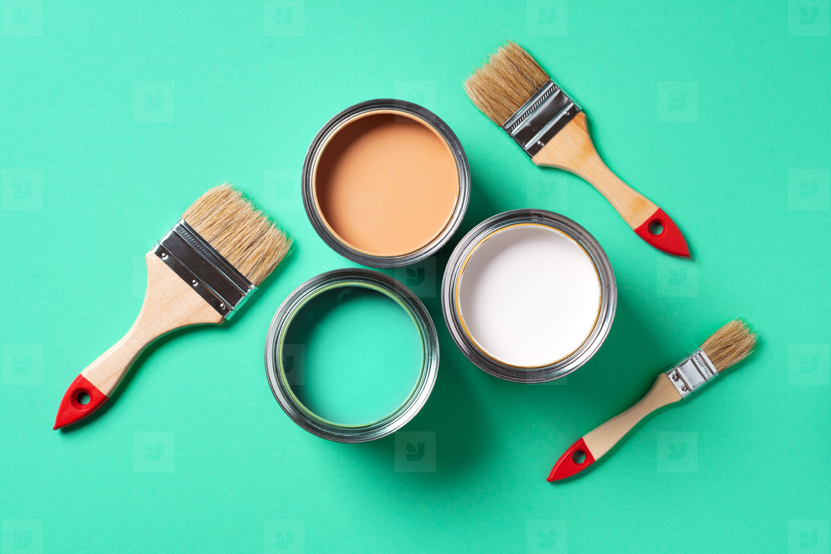 Paint brushes and open paint cans with on trendy green background  Top view  copy space  Appartment renovation  repair  building and home design concept