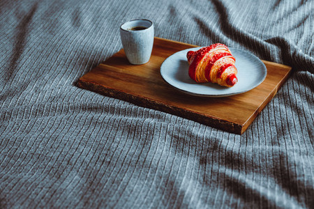 Cherry croissant with a cup of espresso on a wooden tray in a bed Copy space
