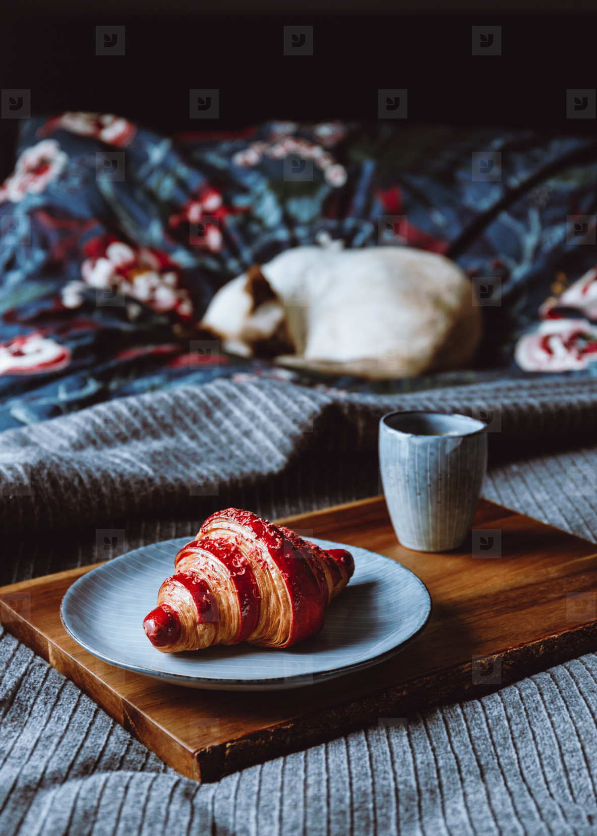 Cherry croissant with a cup of espresso on a wooden tray in a bed  The concept of cozy morning at home