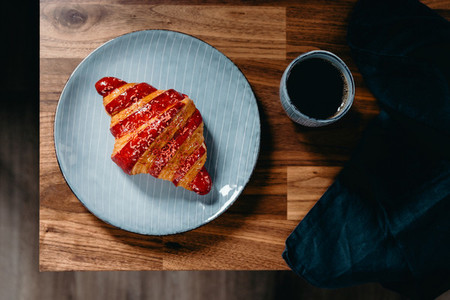 Cherry croissant with a cup of espresso on a rustic wooden table Top view