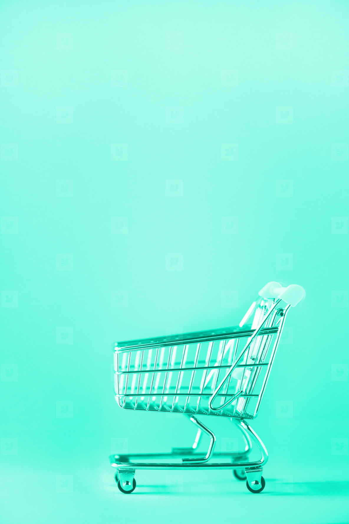 Shopping cart on mint color background  Minimalism style  Creative design  Copy space  Shop trolley at supermarket  Sale  discount  shopaholism concept  Trendy green and turquoise color