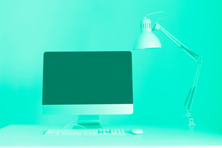 Designer workspace on mint color background  Minimalistic home office  Trendy green and turquoise color  Keyboard  mouse  computer display with black blank screen