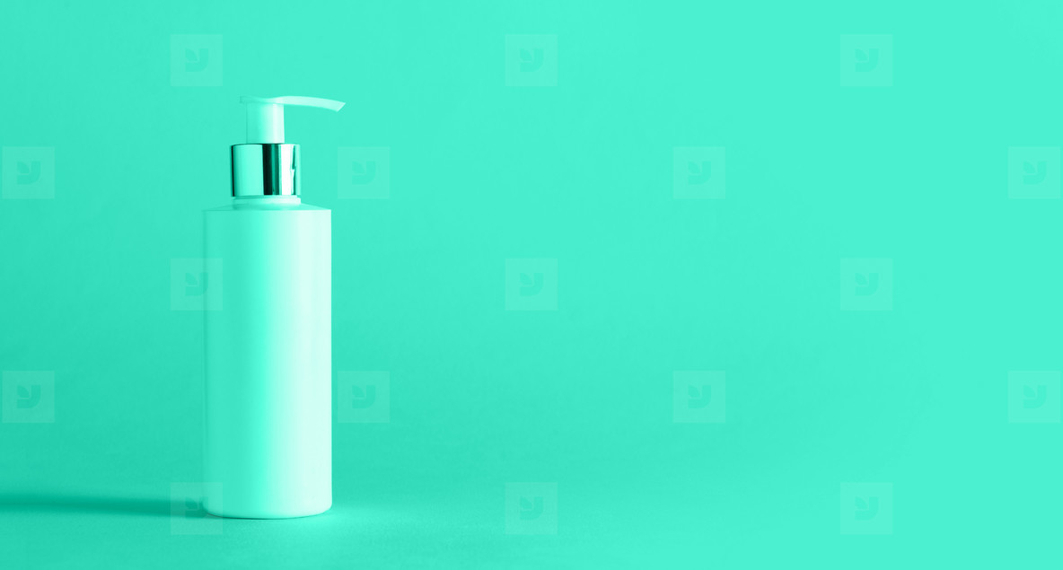 White bottle of moisturizing lotion on mint color background with copy space  Minimalism style  Trendy green and turquoise color  Skin care  body treatment  beauty concept