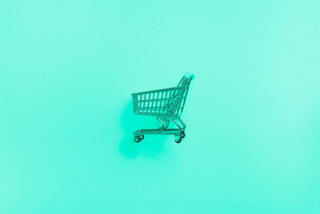Shopping cart on mint color background Minimalism style Shop trolley at supermarket Trendy green and turquoise color Sale discount shopaholism concept Consumer society trend