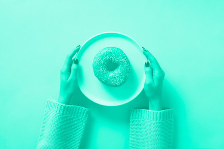 Female hands holding donut on plate over mint color background  Trendy green and turquoise color  Top view  flat lay  Sweet  dessert  diet concept  Weight lost after holidays