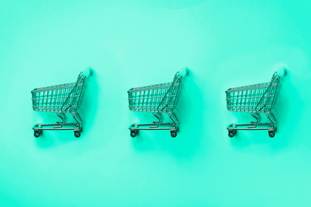 Shopping cart on mint color background  Minimalism style  Creative design  Shop trolley at supermarket  Trendy green and turquoise color  Sale  discount  shopaholism concept