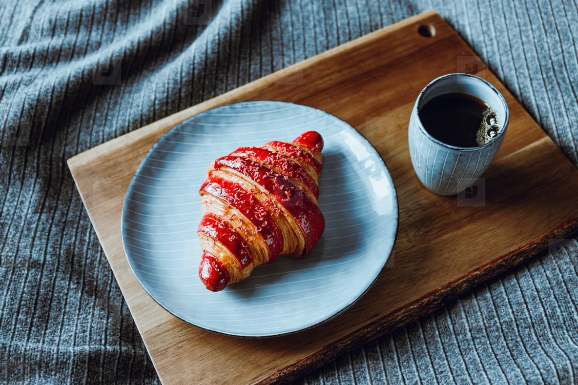 Cherry croissant with a cup of espresso on a wooden tray in a bed