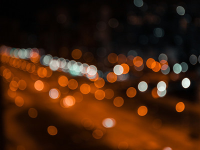 Blurred lights of night city and motion traffic on a highway
