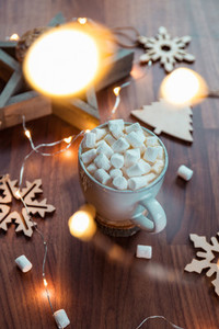 Hot chocolate with marshmallow in a white ceramic mug among winter decor and lights  The concept of cosy holidays and New Year