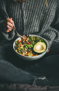 Woman eating fresh salad avocado beans and vegetables from bowl