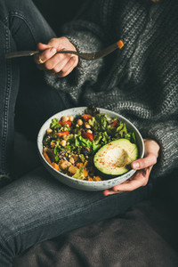 Woman holding bowl with salad  avocado  beans and vegetables