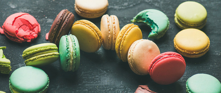 Colorful French macaroons over black background wide composition