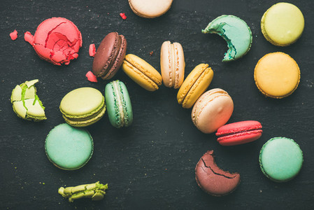 Flat lay of colorful French macaroons over black background