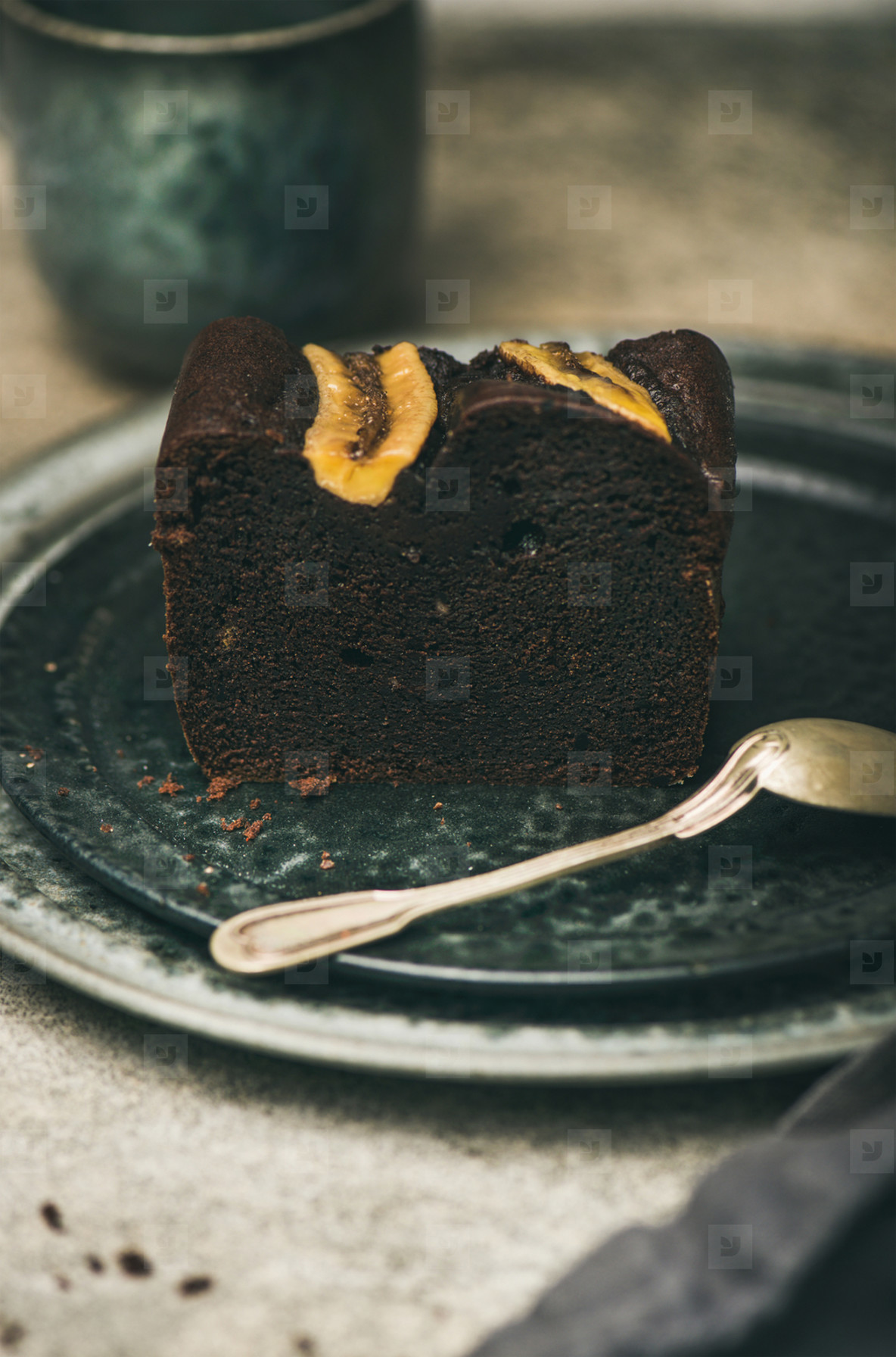 Piece of dark chocolate banana bread cake on grey plate