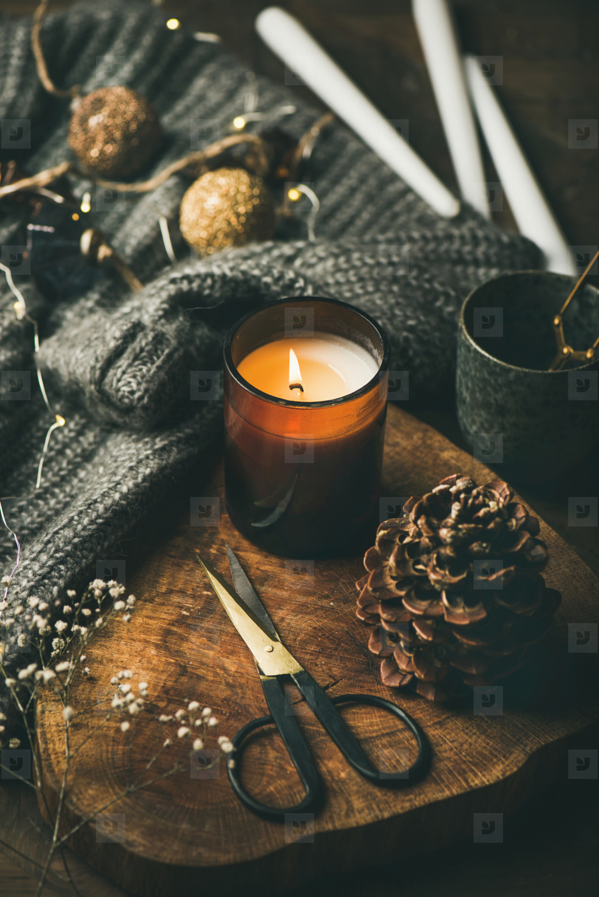 Candle on wooden board  woolen sweater and decoration toys