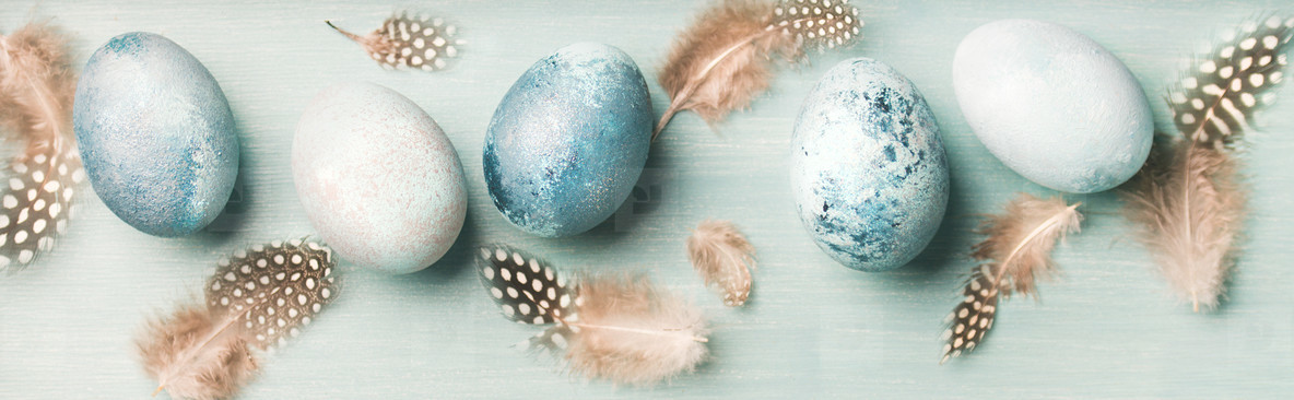 Painted eggs for Easter holiday over light blue background
