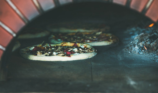 Baking pizzas with cheese and meat in pizza wood oven