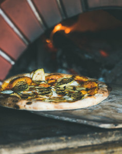 Freshly baked pizza with cheese and mushrooms in pizza oven