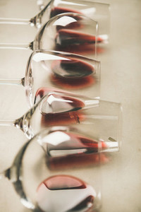 Red wine in different glasses over grey background  selective focus