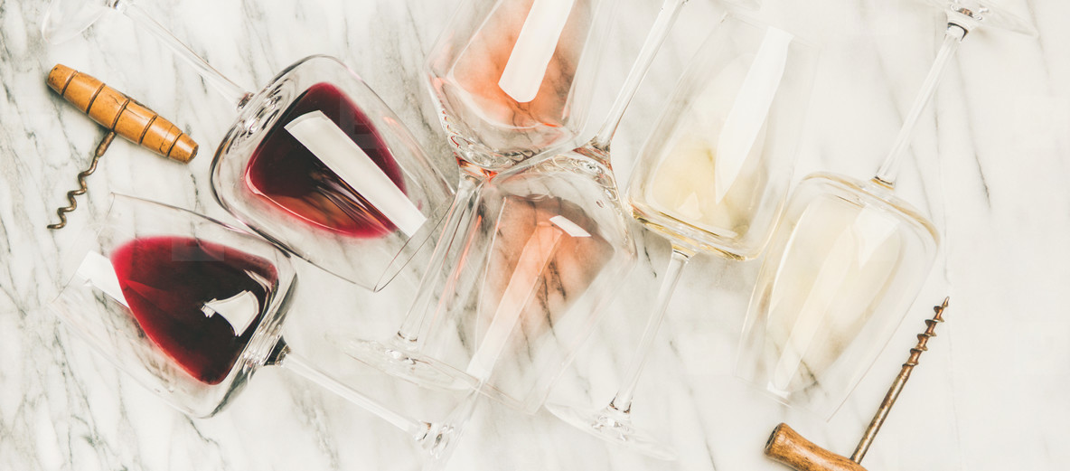Red  rose  white wine in glasses and corkscrews  horizontal composition