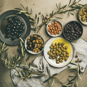 Mediterranean pickled olives and olive tree branches  square crop