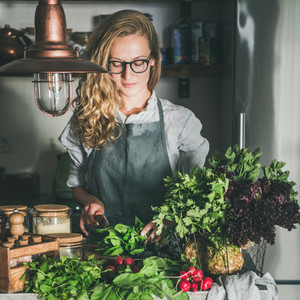 Young woman cutting herbs and vegetables in kitchen  square crop