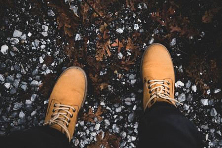 Feet of traveler in yellow boots standing on mountain