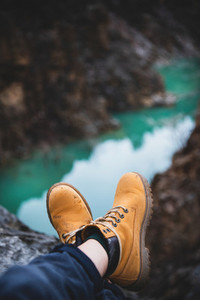 Feet of traveler in boots over chasm with river canyon