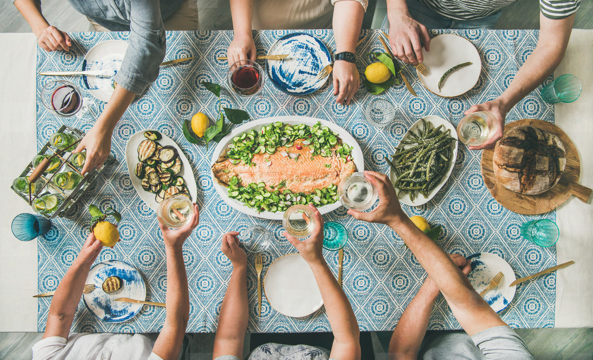 Mediterranean style dinner with cooked salmon and drinks