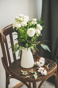 Spring white buttercup flowers in enamel jug on wooden chair