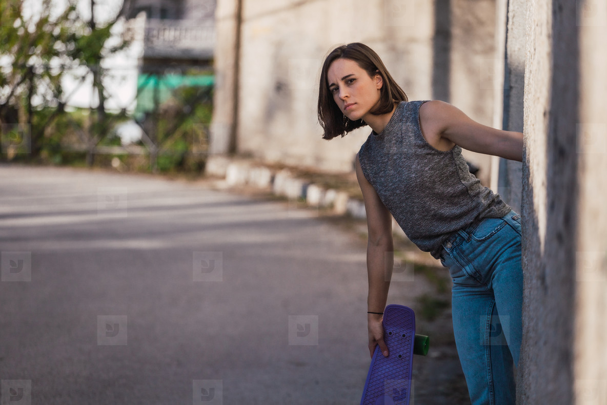 Young woman with blue penny skateboard in casual wearing
